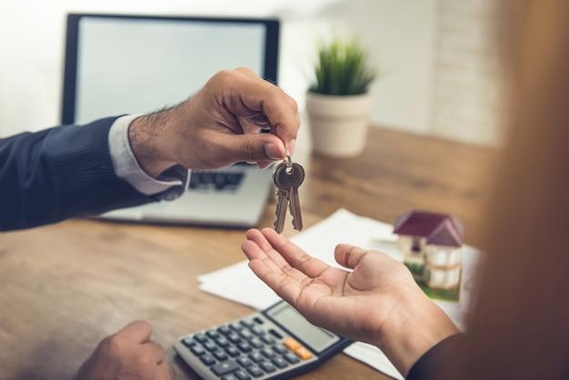 Immobilienmakleragent, der dem kunden hausschlüssel gibt