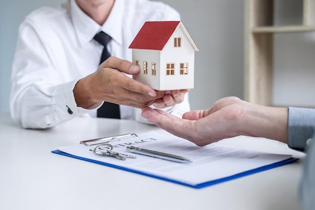 Immobilienmakleragenten, der dem kunden entscheidungsfindungszeichenversicherung vorstellt und berät