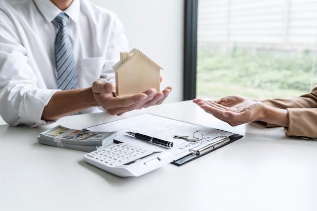 Immobilienmaklerberater konsultieren den kunden, der das versicherungsformular für das zeichen erstellt und das hausmodell sendet
