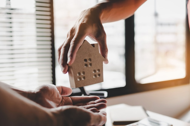 Immobilienmaklermanager, der dem kunden hausmodell gibt