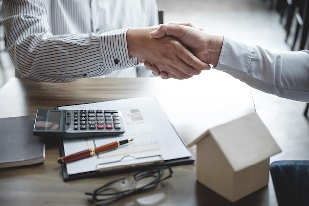 Immobilienmaklervertreter und kunde, die hände rütteln, nachdem vertragsdokumente unterzeichnet worden sind