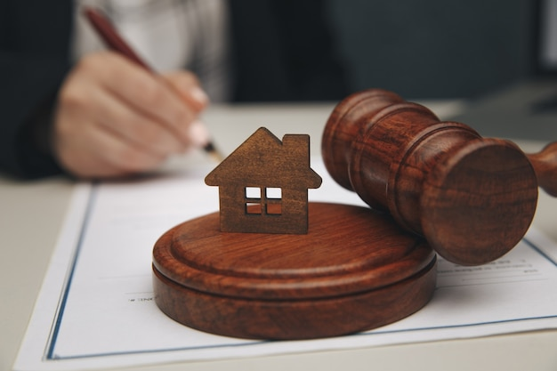 Immobilienrechtliches konzept. modell eines hauses und eines hammers.