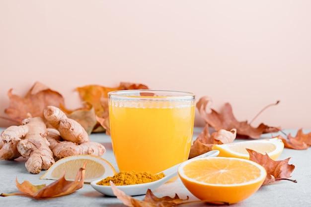 Immunstärkendes getränk mit zitrusfrüchten, ingwer, kurkuma. trinken oder smoothie mit gelben herbstblättern für die herbst- oder virussaison auf neutralem beigem hintergrund, stillleben