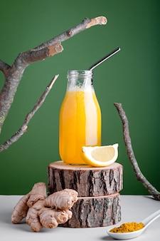 Immunsystem stärkendes getränk oder smoothie mit ingwer, zitrone und kurkuma auf holzständer für den herbst auf grünem hintergrund mit natürlichen elementen. kreatives minimalistisches stillleben
