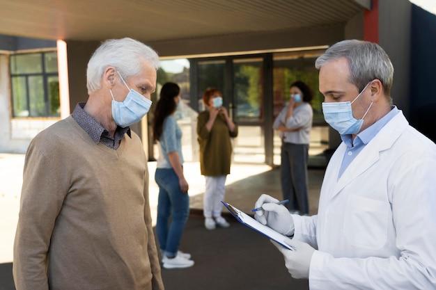 Impfarzt im zentrum füllt patienteninformationen auf dem notizblock aus