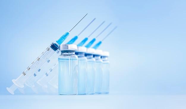 Impfflaschen und spritzen befinden sich in einer reihe auf einer blauen oberfläche