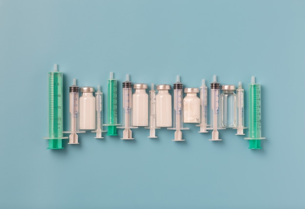 Impfkonzept für die covid-19-pandemie medizinische spritzen ampullen und medikamente auf blauem hintergrund