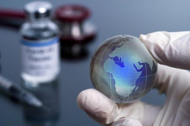Impfkonzept globe glass in der hand eines arztes, der medizinische handschuhe mit verschwommenem coronavirus trägt