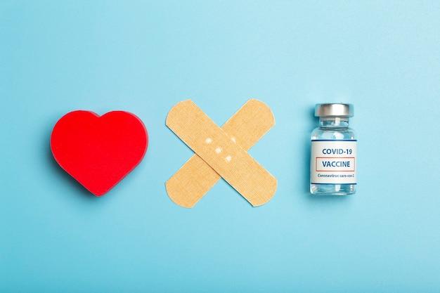 Impfkonzeptampulle mit covid-coronavirus-impfstoff auf blauem medizinischem minimalem hintergrund hoher qualität
