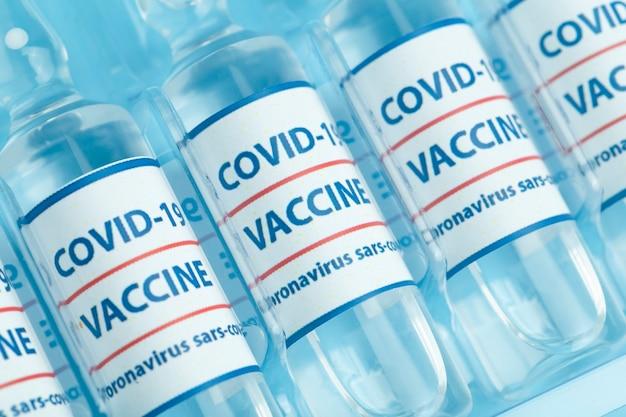 Impfstoff gegen covid-19. medizinische glasfläschchen mit flüssigkeit. ampullen mit coronavirus-impfstoff auf einem medizinischen glastisch