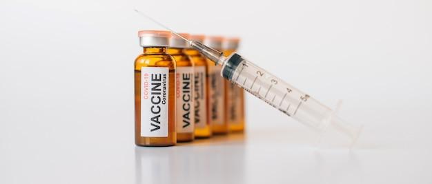 Impfstofffläschchen aus verzinntem glas mit etikett und medizinischer spritze mit nadel auf weißem hintergrund. banner für die werbung für pharmazeutische produkte mit kopienraum.