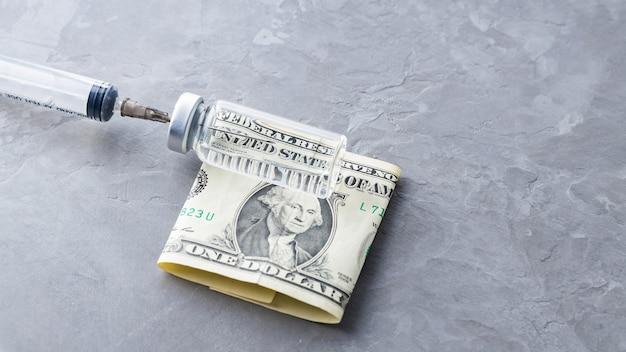 Impfstoffflasche, spritze und dollarschein auf grauem hintergrund