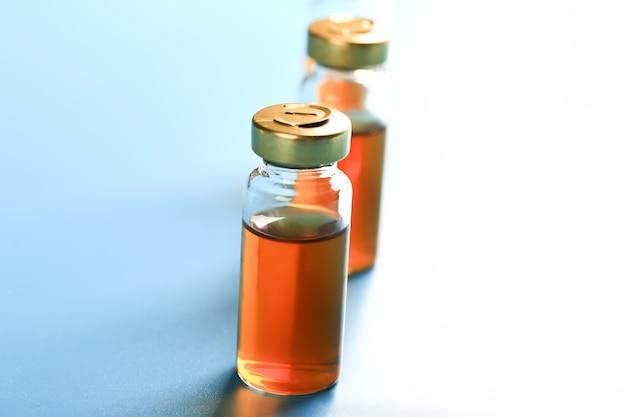 Impfstoffflaschen auf blauem hintergrund medizinisches konzept sehr geringe schärfentiefe beleuchtung über...