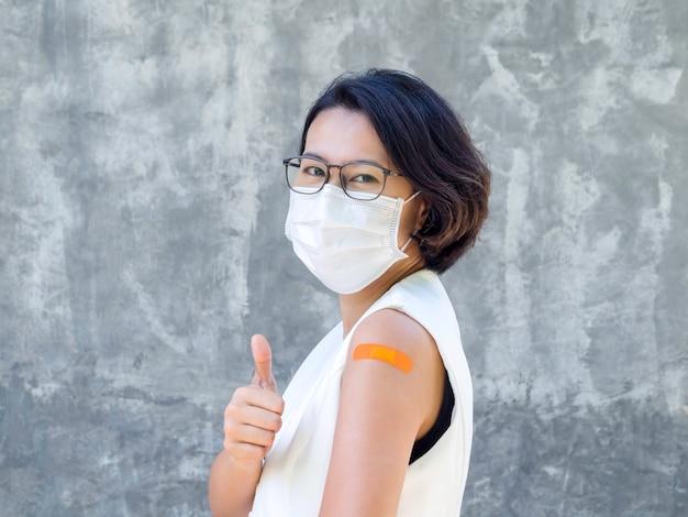 Impfungen, verband am armkonzept geimpfter menschen. fröhliches geschäft asiatische frau mit weißer blazerweste, gesichtsmaske, brille mit orangefarbenem verband und daumen nach oben, nach der impfung.