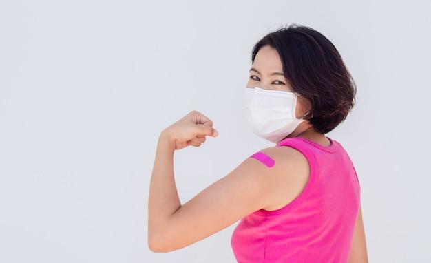 Impfungen, verband auf bannerkonzept für geimpfte menschen. asiatische frau mit maske mit verbandpflaster, die nach der impfung auf weiß mit kopienraum eine starke geste mit der faust zeigt.