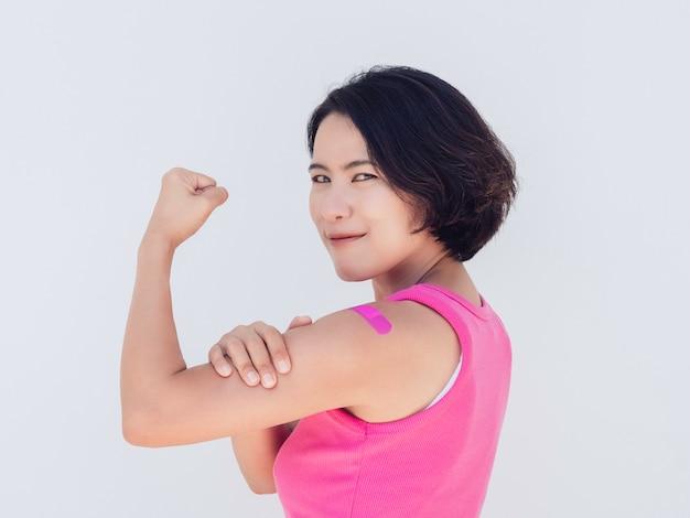 Impfungen, verband auf dem konzept der geimpften menschen. selbstbewusste asiatin in rosafarbenem tanktop mit verbandpflaster, das eine starke geste mit der fausthand nach der impfung isoliert auf weiß zeigt.