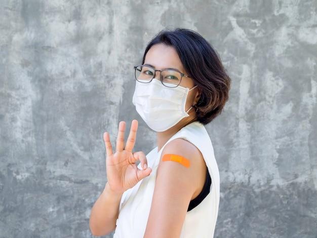 Impfungen, verbandpflaster auf dem armkonzept geimpfter menschen. orangefarbener klebeverband am arm einer geschäftsfrau, die eine weiße gesichtsmaske trägt und nach der impfung ein ok handzeichen zeigt.