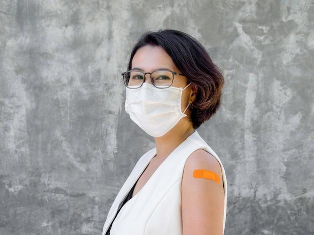 Impfungen, verbandspflaster am arm der geimpften. glückliche geschäftsfrau mit weißer blazerweste, gesichtsmaske und brille mit orangefarbenem verband am arm, nach der impfung.