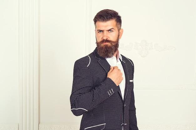Imposanter gut gekleideter mann mit bart in luxuriösen apartments mit klassischem interieur. respektabler junger brutaler mann im anzug, der im weißen raum mit klassischem interieur steht. luxus. männer schönheit, mode.