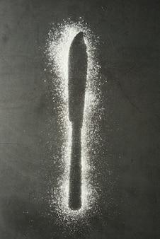Impressum messerschattenbild gemacht vom mehl auf einem schwarzen hintergrund