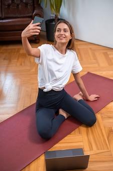 In activewear gekleidet, posiert weibliches model lächelnd vor der kamera und macht fotos auf ihrem smartphone. modernes wohnzimmer mit einigen möbeln.
