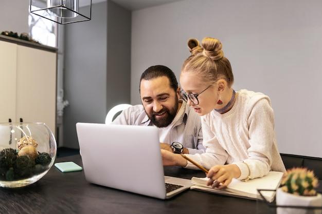 In arbeit. blondes hübsches mädchen in einem weißen pullover, das etwas auf einem laptop tippt, während es eine lektion hat