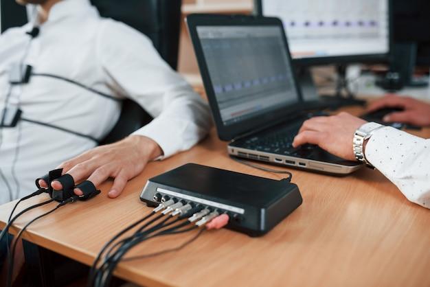 In arbeit. verdächtiger mann übergibt lügendetektor im büro. fragen stellen. polygraphentest