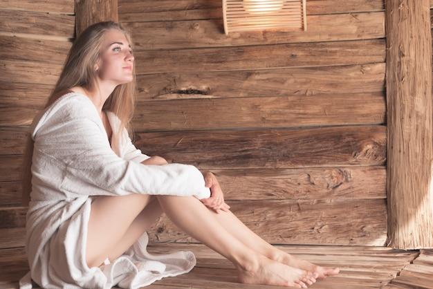 In betracht gezogene schöne junge frau, die in der sauna sich entspannt