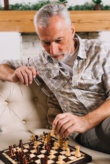 In betracht gezogener älterer mann, der schach spielt