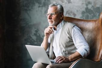 In Betracht gezogener älterer Mann, der auf Stuhl mit Laptop gegen Schmutzhintergrund sitzt