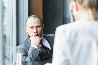 In Betracht gezogener Geschäftsmann, der in cafà sitzt