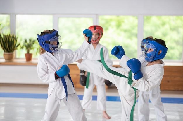 In boxhandschuhen. aktive sportliche jungen und mädchen mit helmen und boxhandschuhen, die sich streiten