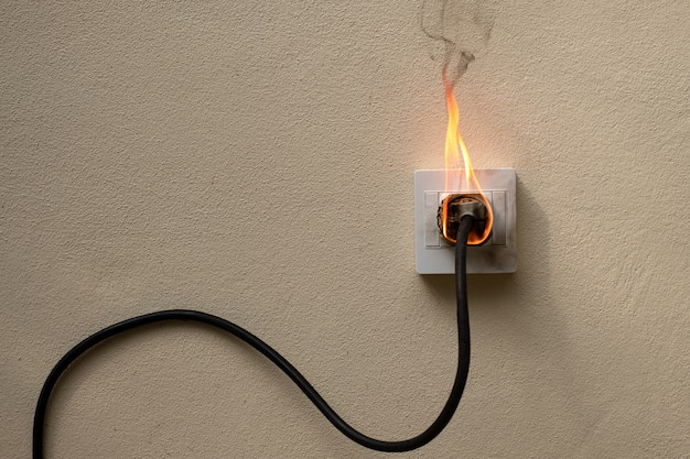 In brand geratener elektrischer kabelstecker buchse an der betonwand sichtbetonhintergrund mit kopierraum