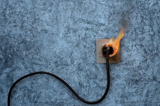 In brand geratener elektrischer kabelstecker buchse an der betonwand