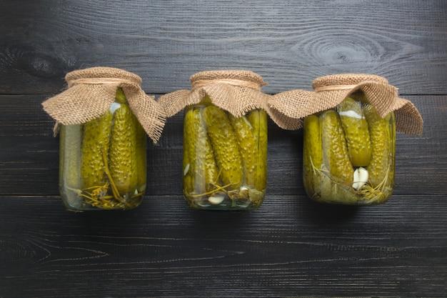 In büchsen konservierte gemüsegurke in den glasgefäßen auf woodeb dunklem brett. sicht von oben. hausgemachte herbstvorbereitungen. hausaufgaben und traditionen.