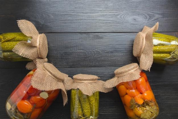 In büchsen konservierte gemüsegurke und -tomate in den glasgefäßen auf woodeb dunklem brett. sicht von oben. verschiedene arten von dosen. hausaufgaben und traditionen.