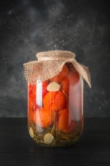 In büchsen konservierte gemüsetomate in den glasgefäßen auf schwarzem hölzernem brett. hausgemachte ernte- und herbstvorbereitungen.