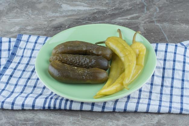 In büchsen konservierte gurken und grüne peperoni auf grüner platte.