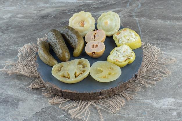 In büchsen konservierte hausgemachte essiggurken auf holzbrett über grauem tisch.