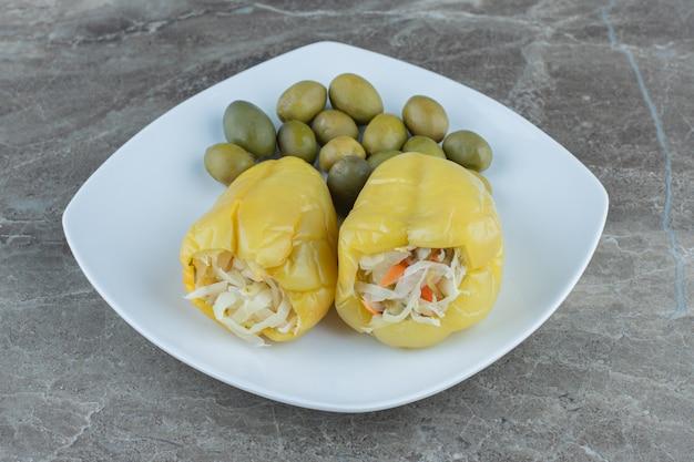 In büchsen konservierte paprika gefüllt mit sauerkraut mit olive auf weißem teller.