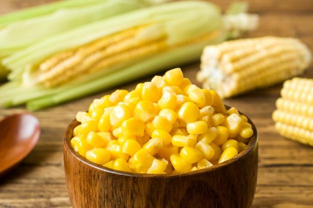 In büchsen konservierter mais in einer hölzernen platte und in einem pfeiler von frischem mais auf einem rustikalen hölzernen hintergrund