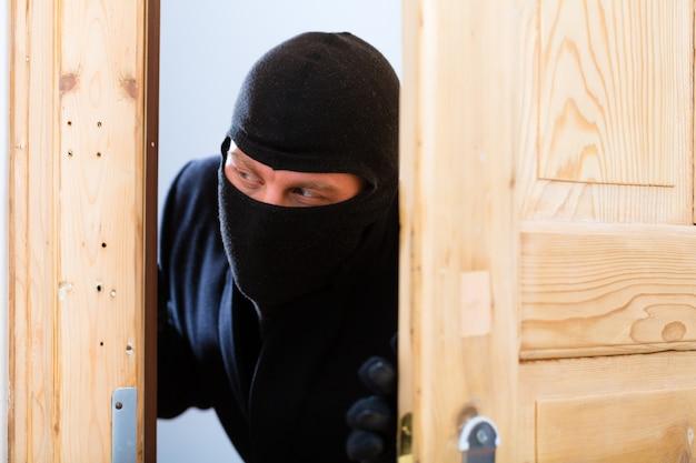 In burglary crime öffnet ein einbrecher eine tür