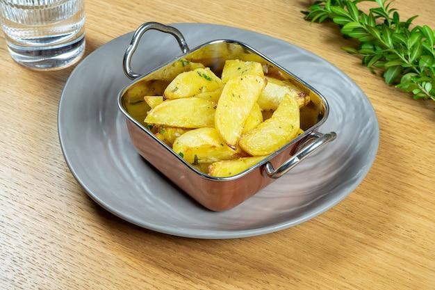 In butterkartoffelschnitzen mit rosmarin in goldener schüssel geröstet. nahansicht. veganes essen. leckere beilage. selektiver fokus. lebensmittelfoto für rezept oder menü. straßenessen