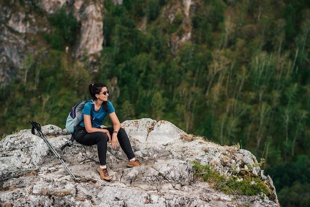 In den bergen wandern. ein ausflug in die berge. tourist in den bergen. aktives freizeitkonzept. reisende frau mit rucksack auf dem hintergrund der berge. glücklicher mädchenreisender. platz kopieren