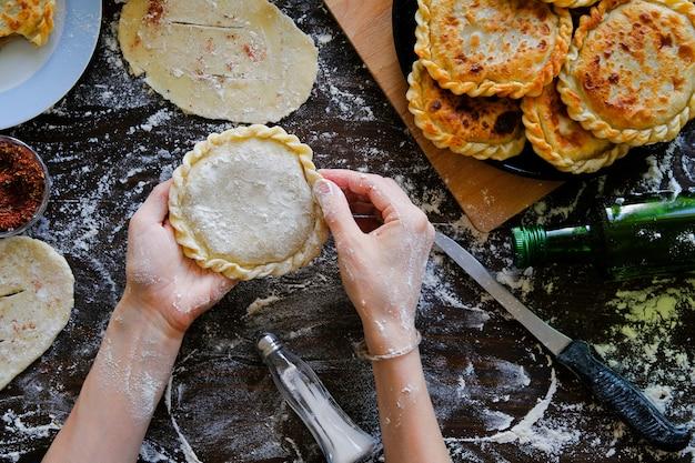 In den händen des georgischen flachen kuchens des kochs des rohen teigs auf dem hintergrund eines holztischs, besprüht mit mehl. eine frau kocht eine torte oder khachapuri. in der nähe von lebensmitteln, küchenutensilien. familienleben.