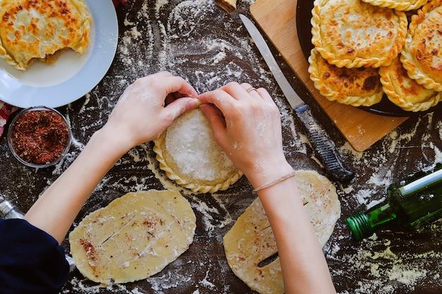 In den händen des kochs georgisches brot aus rohem teig. eine frau macht einen kuchen oder khachapuri.