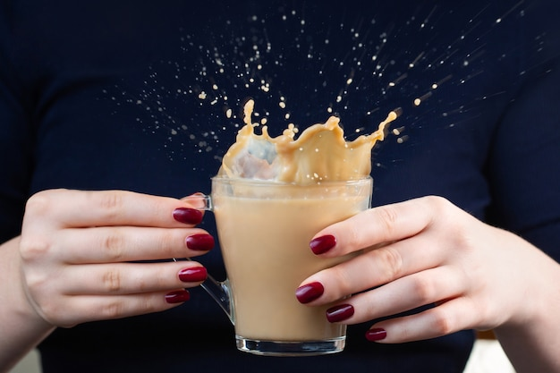 In den händen des mädchens eine tasse kaffee mit milch. kaffeespray. splash schöne formen aus kaffeespritzern. rote maniküre. frühstückszeit.