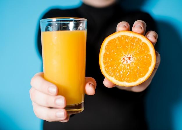 In den händen einer orange und saft. gesunder lebensstil.