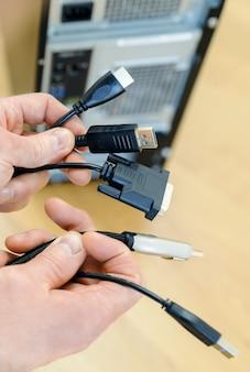 In den händen eines mannes befinden sich verschiedene kabel und stecker.