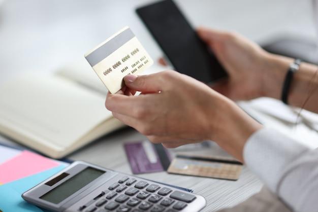 In den händen von kreditkarte und smartphone